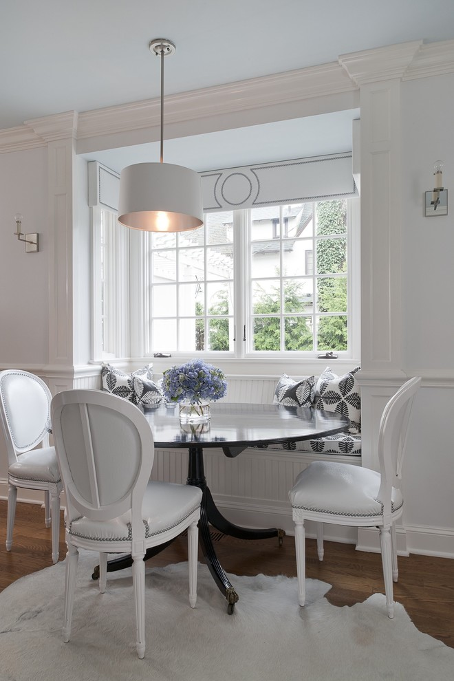 Example of a small classic medium tone wood floor kitchen/dining room combo design in New York with white walls and no fireplace