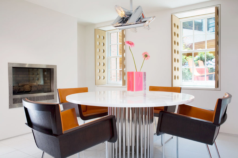 Trendy dining room photo in New York with white walls and a standard fireplace