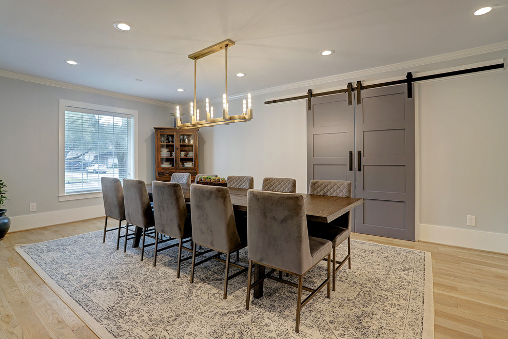 Example of a mid-sized transitional light wood floor and beige floor enclosed dining room design in Houston with gray walls