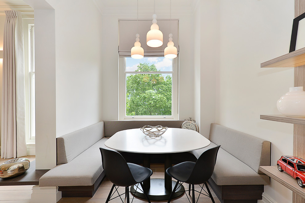Photo of a scandi dining room in London with white walls, light hardwood flooring and no fireplace.