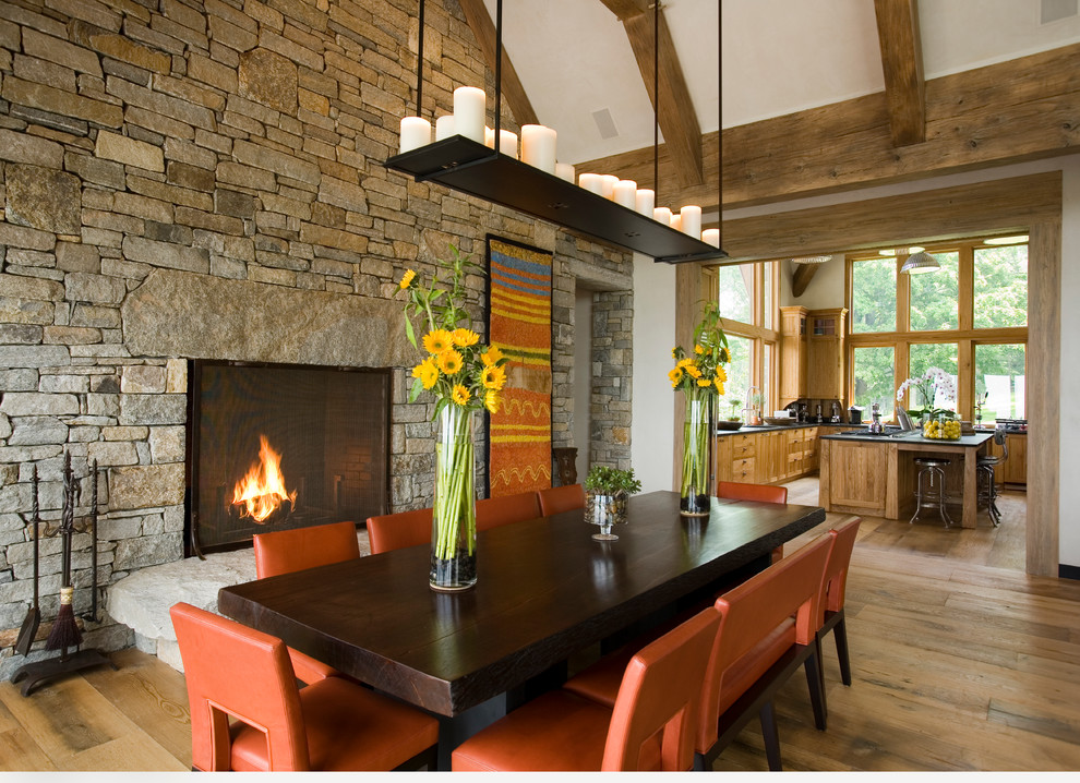 Inspiration for a rustic medium tone wood floor dining room remodel in New York with white walls, a standard fireplace and a stone fireplace