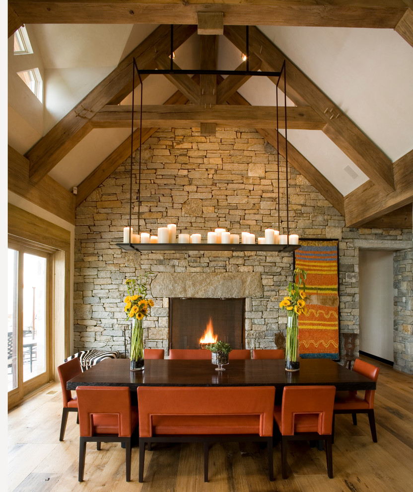 Dining room - rustic medium tone wood floor dining room idea in New York with white walls, a standard fireplace and a stone fireplace