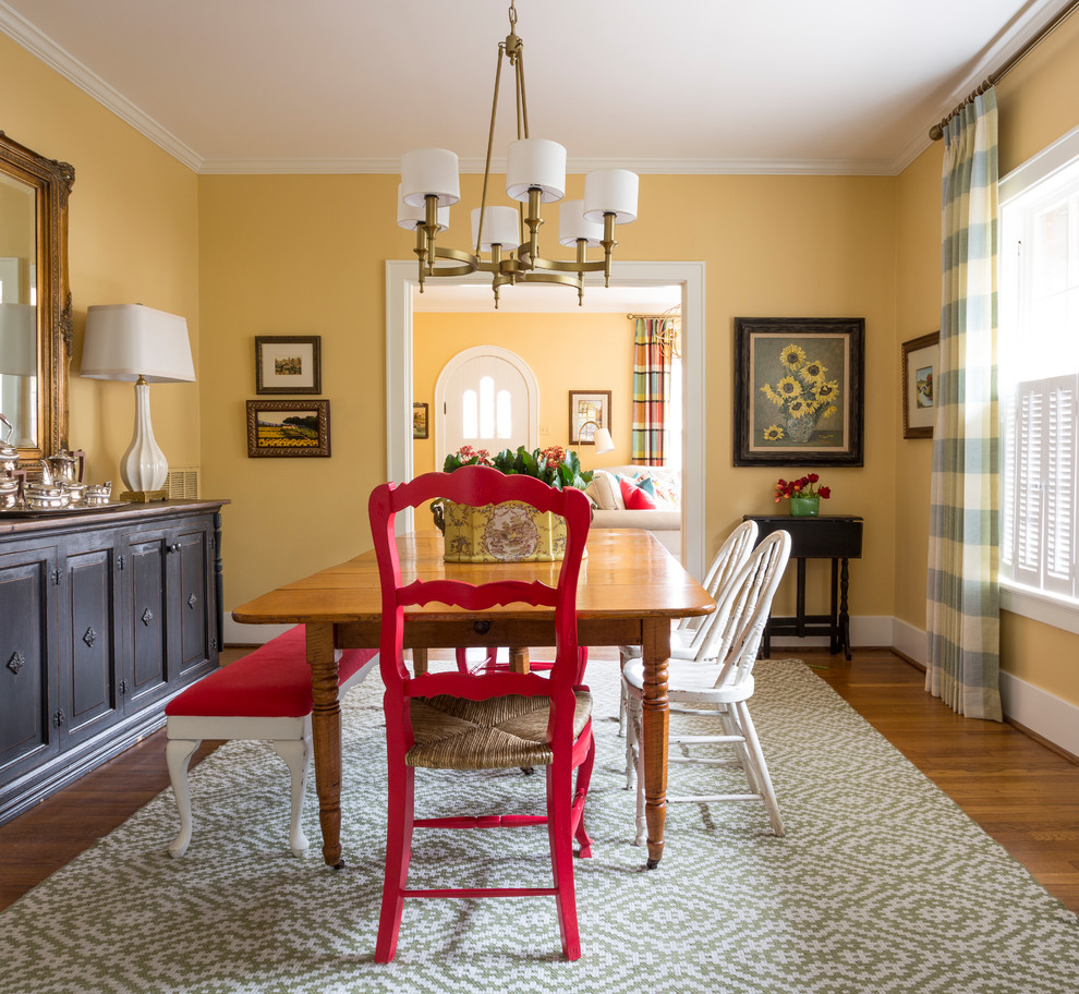 Example of an eclectic medium tone wood floor and brown floor dining room design in Little Rock with yellow walls