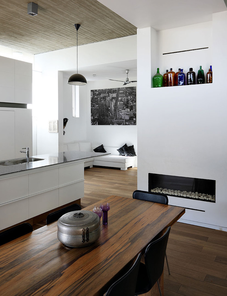 Mid-sized minimalist dark wood floor dining room photo in Tel Aviv with white walls, a ribbon fireplace and a plaster fireplace
