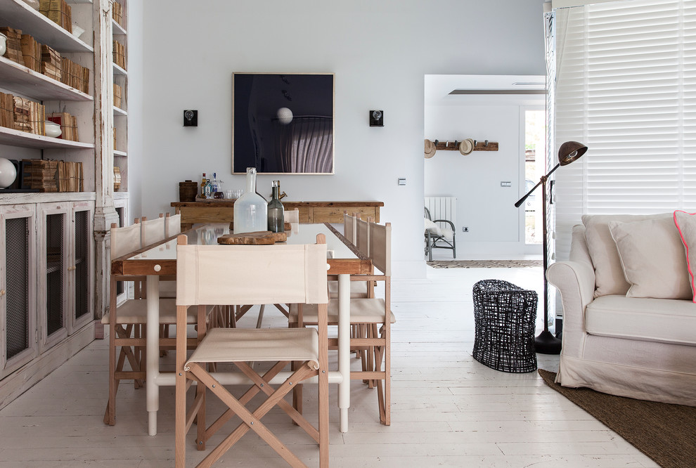 Example of a large danish painted wood floor enclosed dining room design in Madrid with white walls and no fireplace