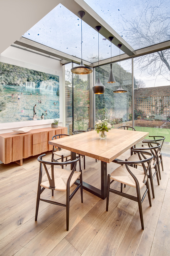 Inspiration for a contemporary medium tone wood floor dining room remodel in London with white walls