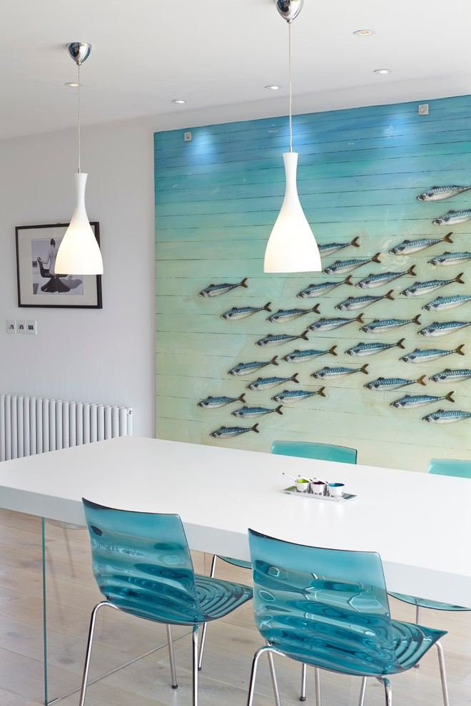 Design ideas for a beach style dining room in Hampshire with white walls and light hardwood flooring.