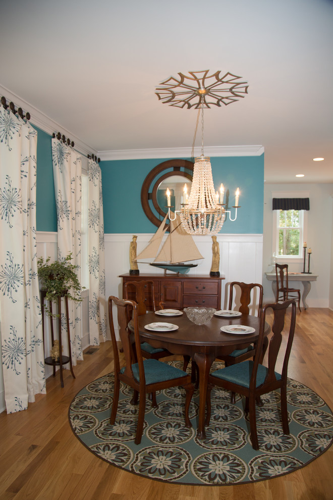 Example of a beach style medium tone wood floor dining room design in Other with blue walls