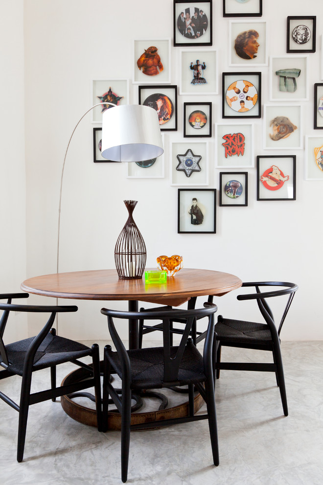 Eclectic concrete floor dining room photo in London with white walls