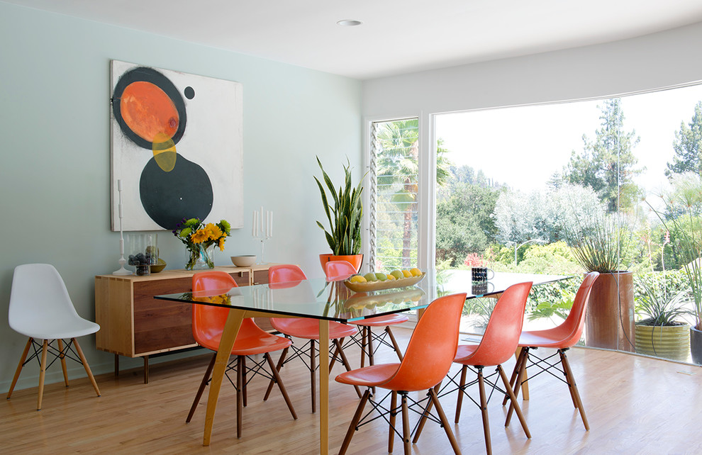 Example of a large mid-century modern light wood floor and brown floor dining room design in Los Angeles with green walls and no fireplace