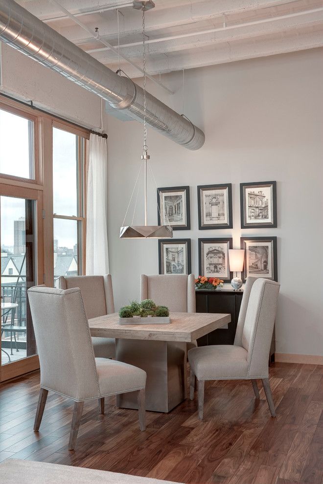 Example of a small urban medium tone wood floor and brown floor dining room design in Milwaukee with gray walls and no fireplace
