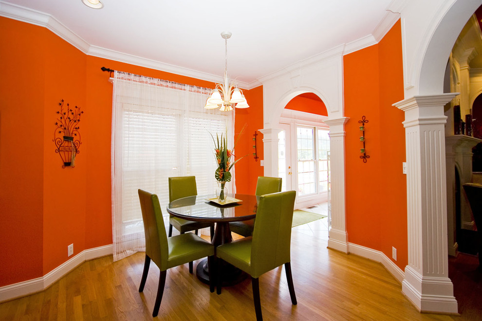 Example of an eclectic medium tone wood floor dining room design in Other with orange walls