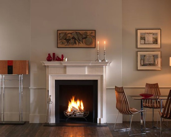 Kedleston - The Kedleston is a handsome chimneypiece that employs sparing detail to achieve its effect. The fluted frieze panels flank a plain centre tablet that sits beneath a breakfront corniced shelf. Carved in limestone, it is shown with the forged steel Morris fire basket and Reeded cast iron interior panels, black slate hearth and slilps.