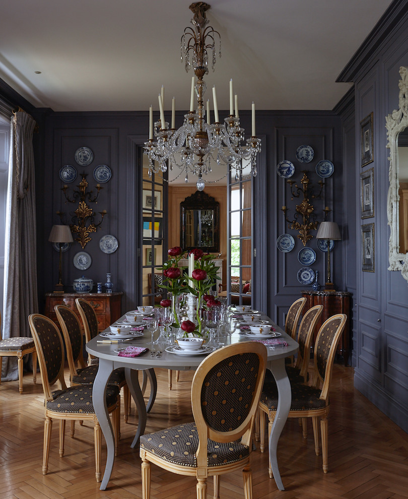 Example of a large classic medium tone wood floor and brown floor enclosed dining room design in London with blue walls