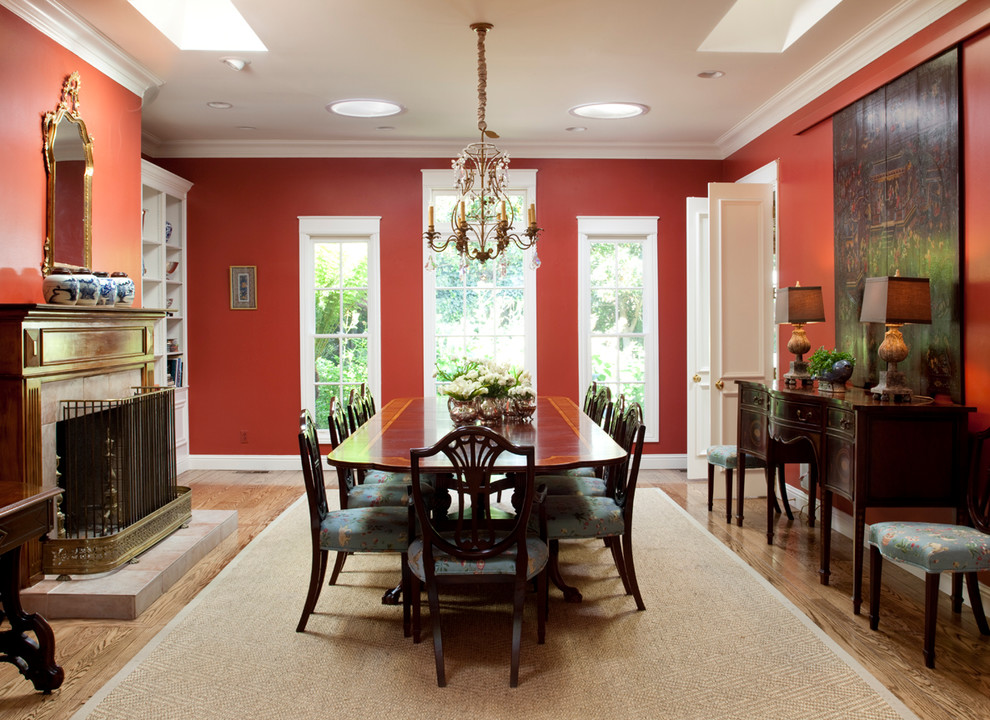 Enclosed dining room - mid-sized traditional medium tone wood floor enclosed dining room idea in San Francisco with red walls, a standard fireplace and a tile fireplace
