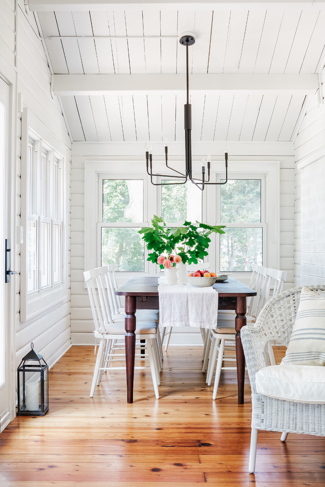 Example of a small beach style medium tone wood floor and brown floor dining room design in Toronto with white walls