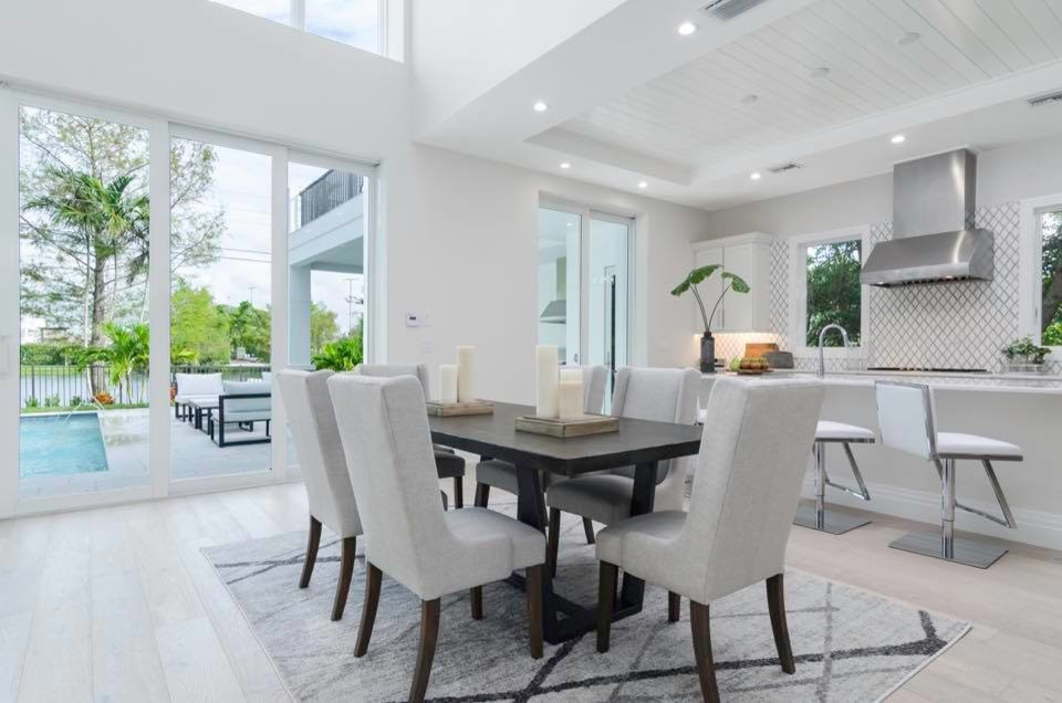 Great room - mid-sized contemporary light wood floor and gray floor great room idea in Miami with white walls, a standard fireplace and a stone fireplace