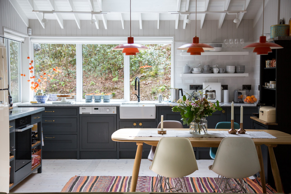 Example of a mid-sized cottage kitchen/dining room combo design in London with white walls