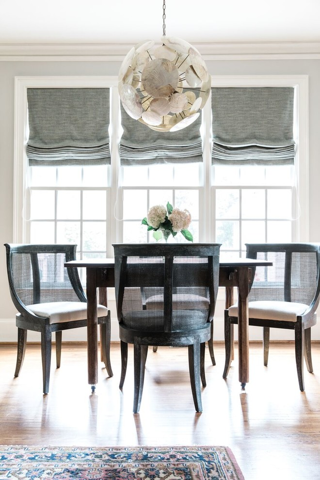 Dining room - transitional medium tone wood floor and brown floor dining room idea in Charlotte with gray walls