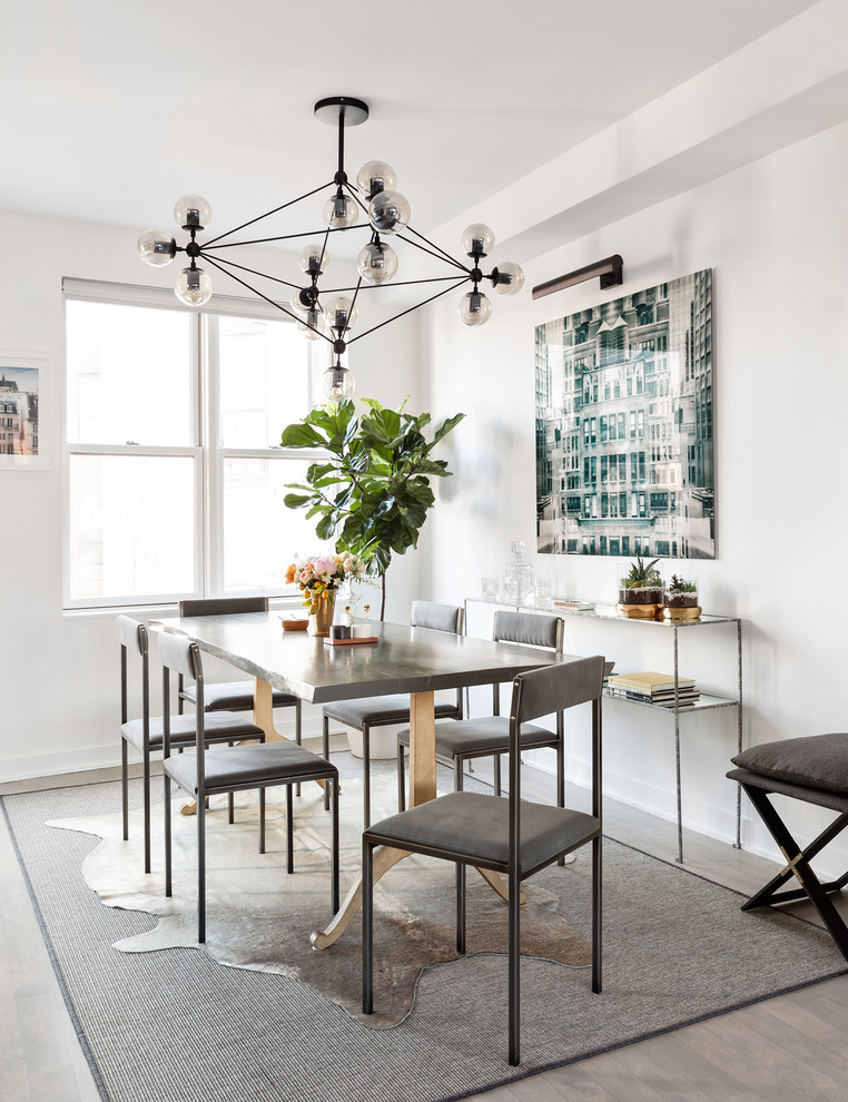 Example of a transitional light wood floor dining room design in New York with white walls
