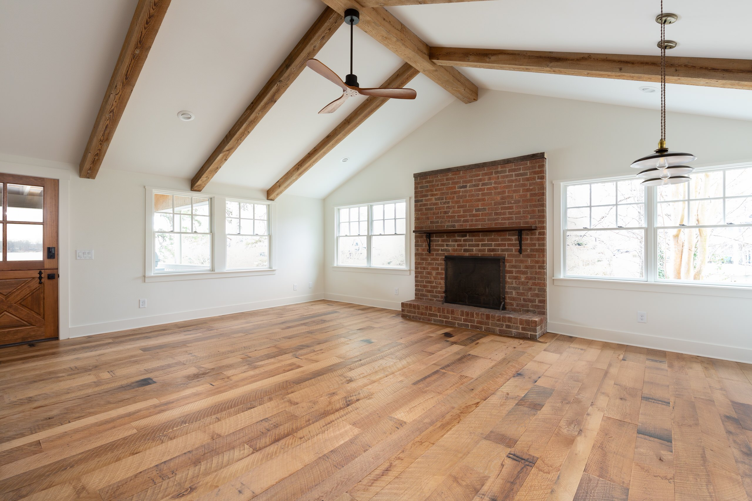 Living room and dining room with reclaimed wood beams on vaulted ceiling