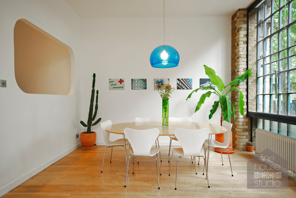 Example of a mid-sized urban light wood floor kitchen/dining room combo design in London with white walls
