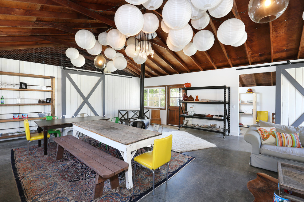 Example of a large island style concrete floor great room design in Orange County with white walls