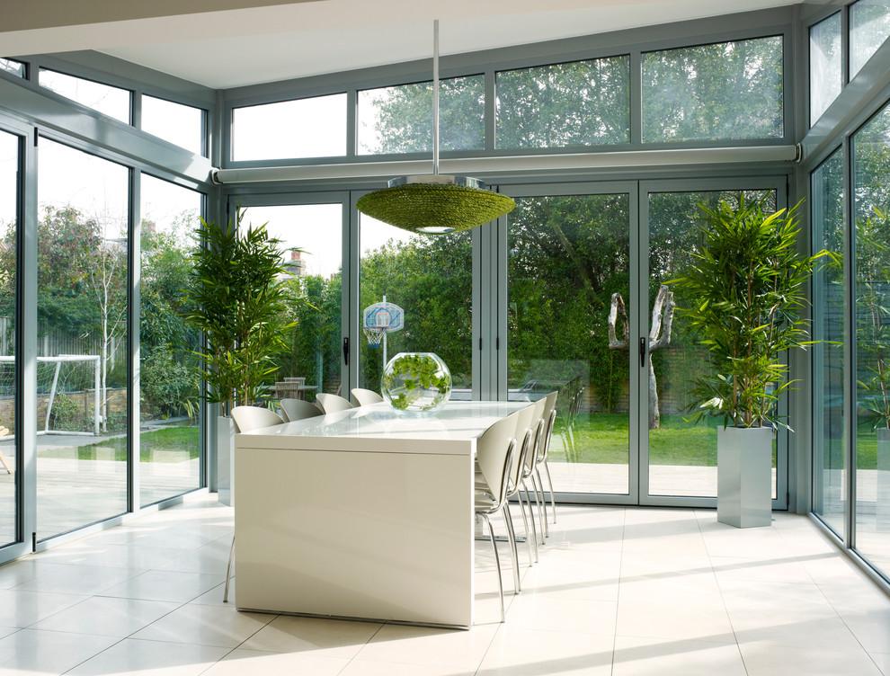 Inspiration pour une salle à manger ouverte sur la cuisine design de taille moyenne avec un mur gris, un sol en carrelage de porcelaine, une cheminée double-face et un manteau de cheminée en plâtre.