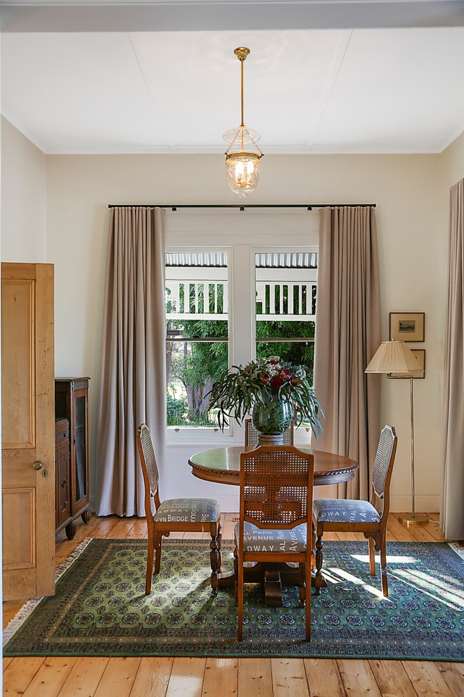 Transitional medium tone wood floor and brown floor dining room photo in Geelong with beige walls