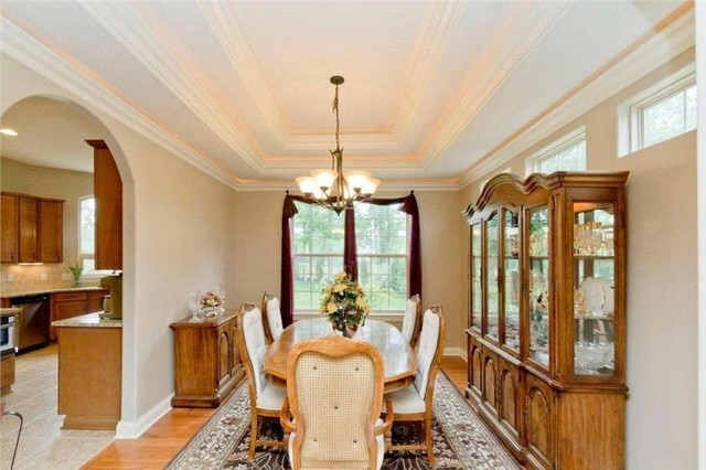 Example of a large classic light wood floor enclosed dining room design in Columbus with beige walls
