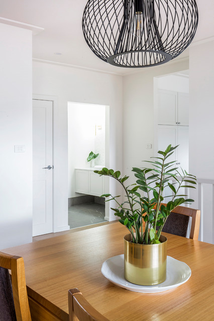Photo of a mid-sized contemporary kitchen/dining combo in Sydney with white walls, painted wood floors and black floor.