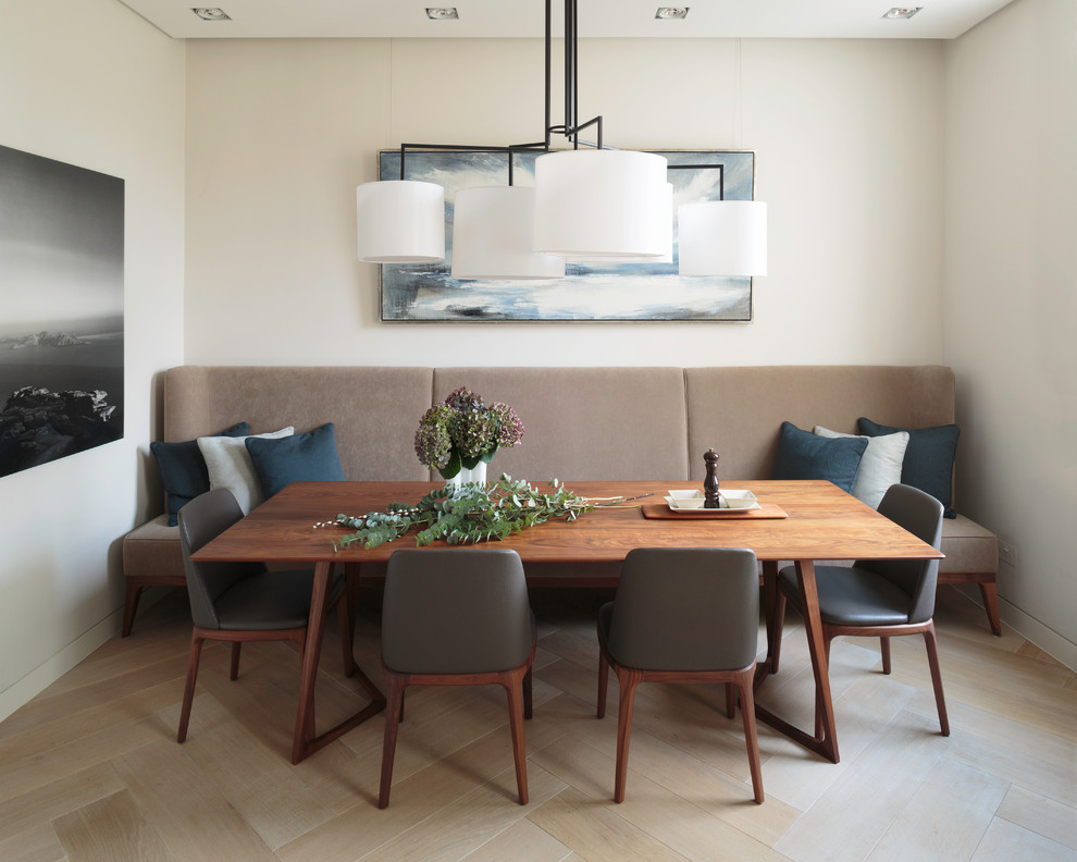 Example of a 1960s light wood floor dining room design in London with white walls