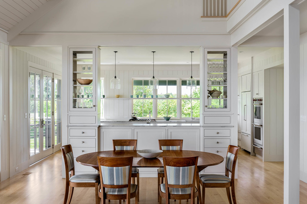 Kitchen/dining room combo - mid-sized coastal light wood floor kitchen/dining room combo idea in Portland Maine with white walls