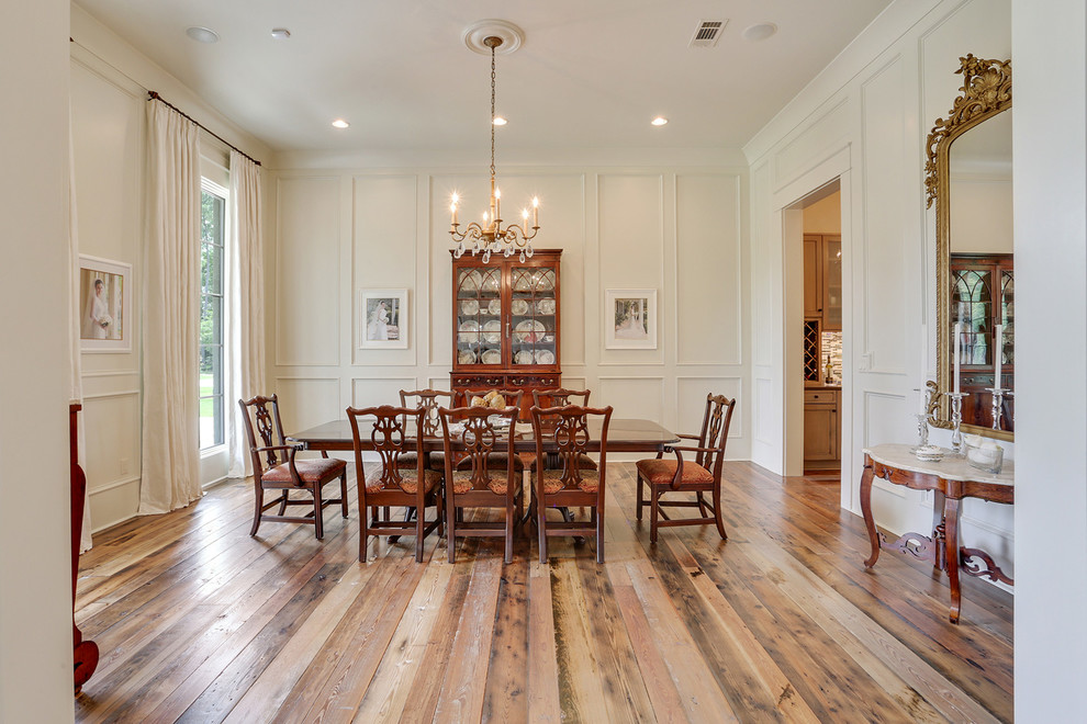 Inspiration for a timeless medium tone wood floor dining room remodel in New Orleans with white walls and no fireplace