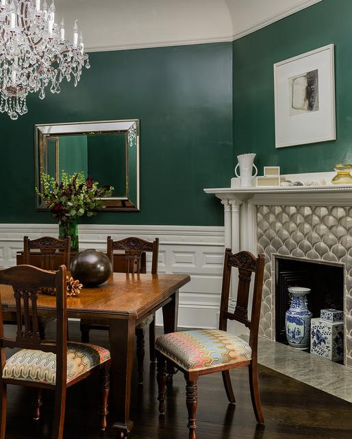Klassisk inredning av en stor separat matplats, med gröna väggar, mörkt trägolv, en standard öppen spis, en spiselkrans i gips och brunt golv