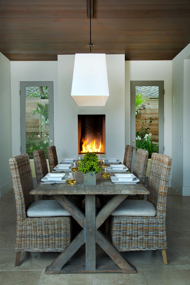 Inspiration for a mediterranean dining room remodel in San Diego with white walls and a standard fireplace