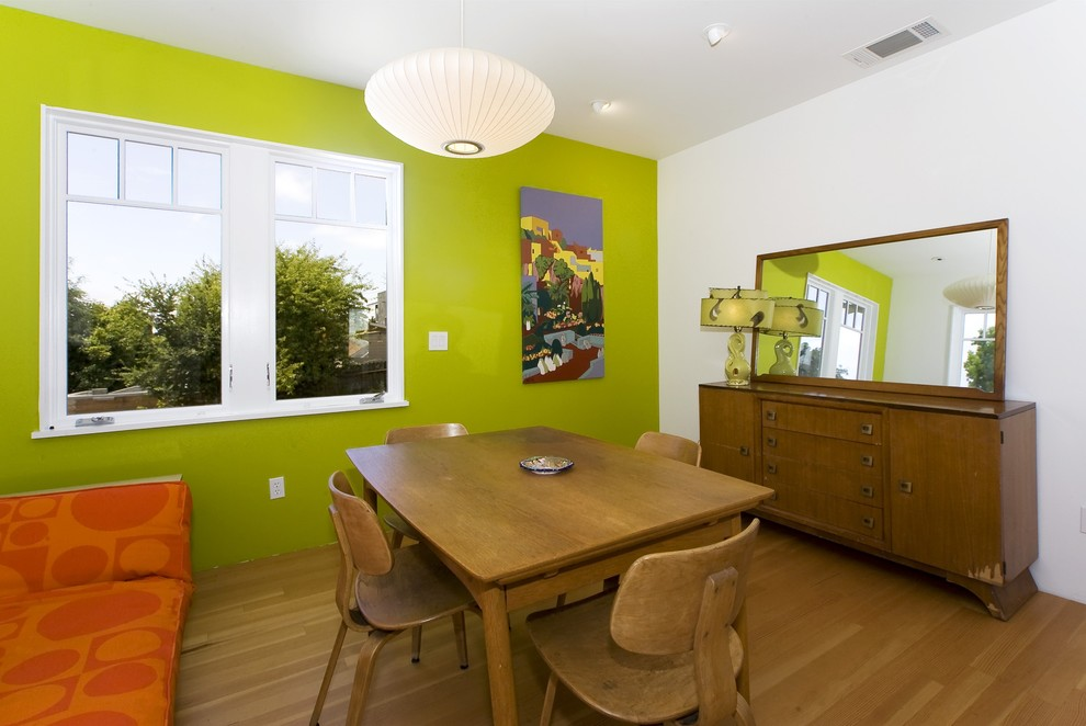 Example of a 1950s medium tone wood floor dining room design in San Francisco with green walls