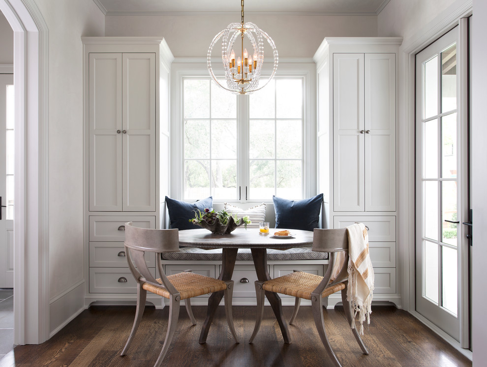Example of a transitional dark wood floor enclosed dining room design in Austin with white walls
