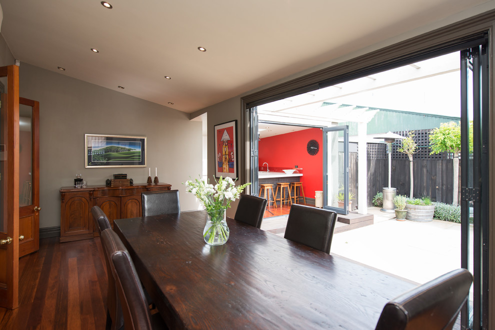 This is an example of a contemporary separate dining room in Christchurch with grey walls and medium hardwood floors.