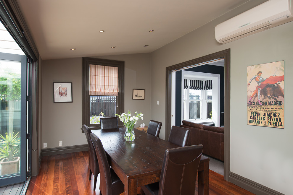 Contemporary separate dining room with grey walls and medium hardwood floors.