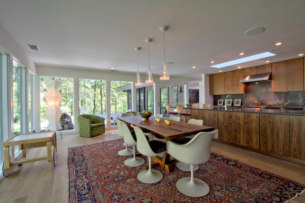 Cette photo montre une salle à manger ouverte sur le salon rétro de taille moyenne avec un mur blanc, un sol en bois clair et un sol beige.