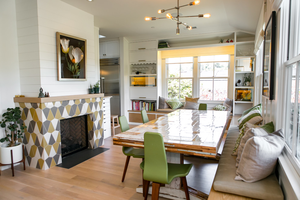 Example of a transitional medium tone wood floor and brown floor kitchen/dining room combo design in San Francisco with white walls, a standard fireplace and a tile fireplace