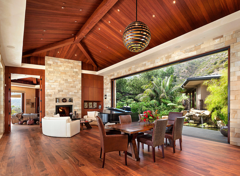 Dining room - huge tropical dark wood floor dining room idea in Santa Barbara with beige walls, a stone fireplace and a standard fireplace