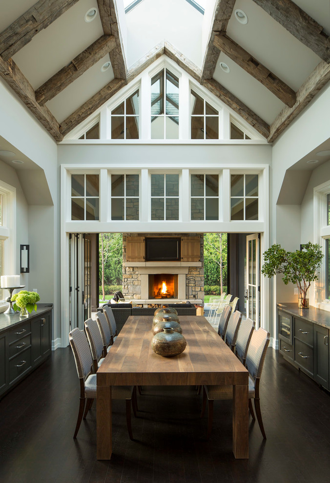 Inspiration for a transitional dark wood floor enclosed dining room remodel in Minneapolis with gray walls and a stone fireplace
