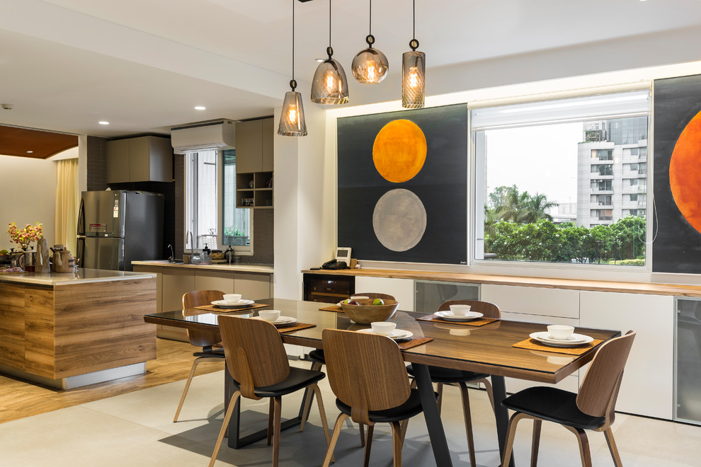 This is an example of a contemporary kitchen/dining room in Delhi with white walls and grey floors.