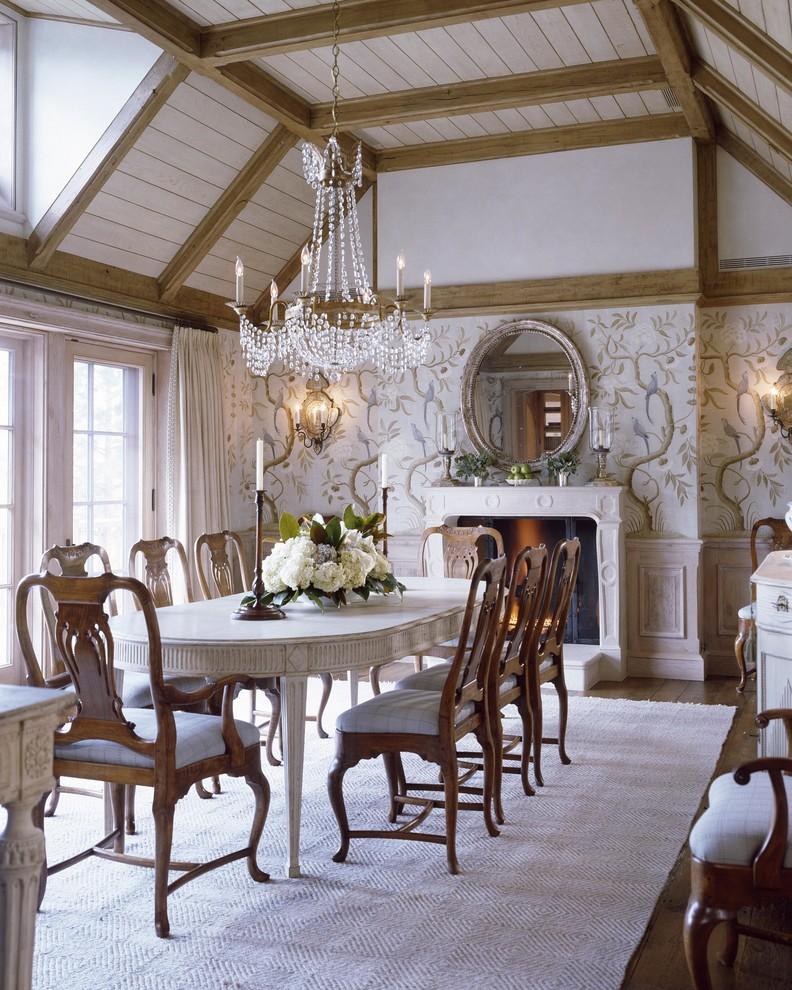 Exemple d'une salle à manger chic fermée avec un mur blanc et une cheminée standard.