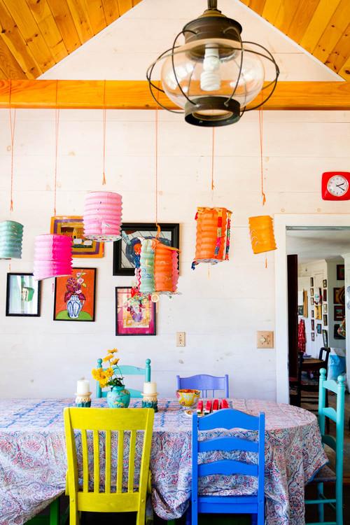 luminárias de papel, teto de madeira, cadeiras coloridas na sala de jantar