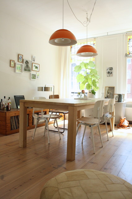 Example of a danish medium tone wood floor dining room design in Amsterdam with white walls