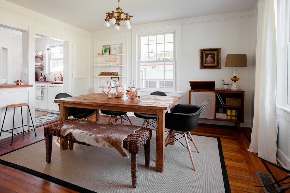 Inspiration for a farmhouse medium tone wood floor and brown floor enclosed dining room remodel in Charleston with white walls