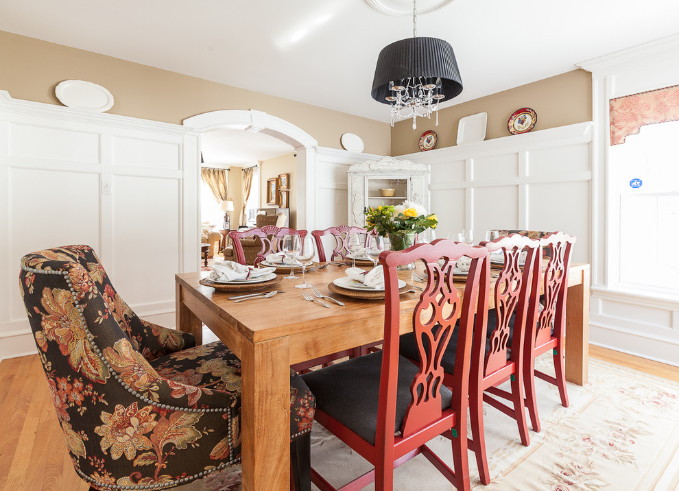 Example of an ornate medium tone wood floor dining room design in Other with beige walls